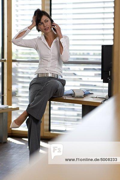 Brünette Frau auf dem Schreibtisch telefoniert
