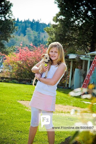 young girl holding puppy outdoors