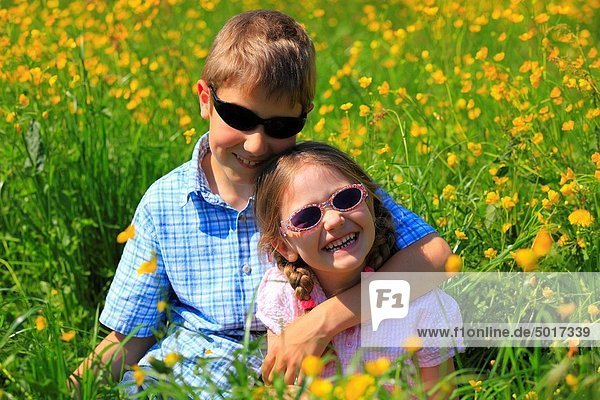 boy and girl sitting in blooming field