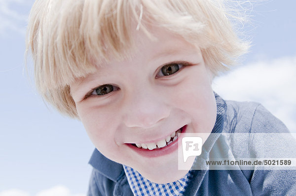 Blonder Junge spielt draußen