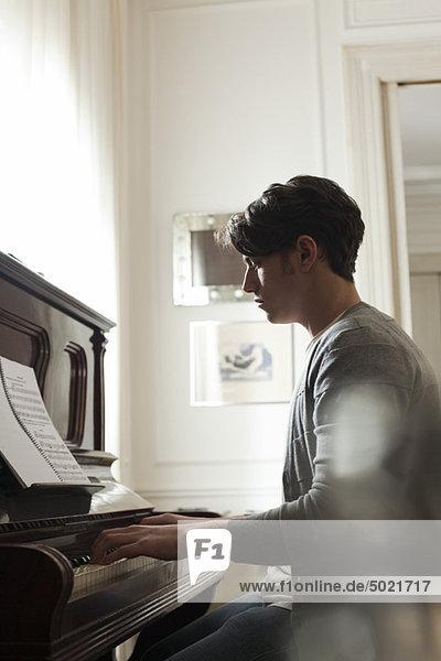 Junger Mann spielt Klavier