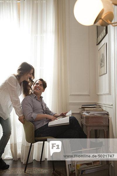 Ein Paar redet  während es sich das Magazin ansieht.