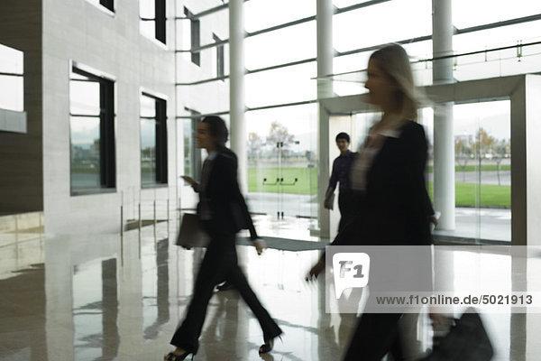 Führungskräfte  die in der Lobby spazieren gehen