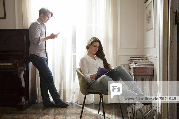 Paar entspannt zu Hause  Frau liest Magazin  Mann schaut auf Handy