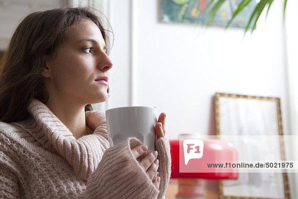 Junge Frau hält Kaffeetasse,  schaut in Gedanken weg
