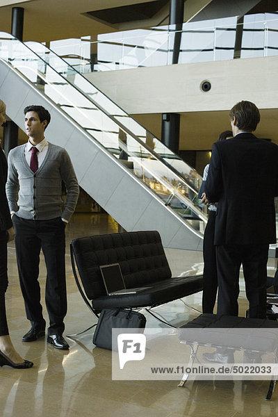 Führungskräfte im Gespräch in der Lobby nach dem Meeting