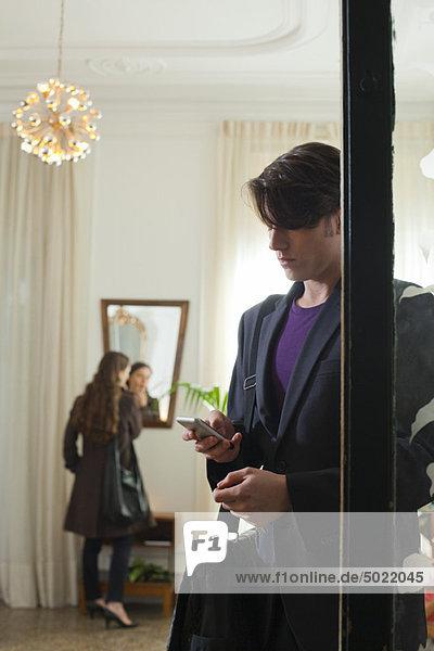 Mann wartet in der Tür mit Handy in der Hand  während die Frau im Hintergrund primpt.