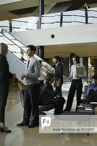 Führungskräfte chatten in der Lobby nach dem Meeting