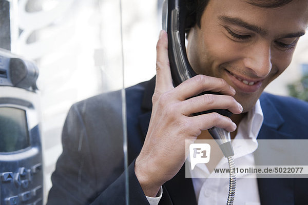 Mann mit Münztelefon