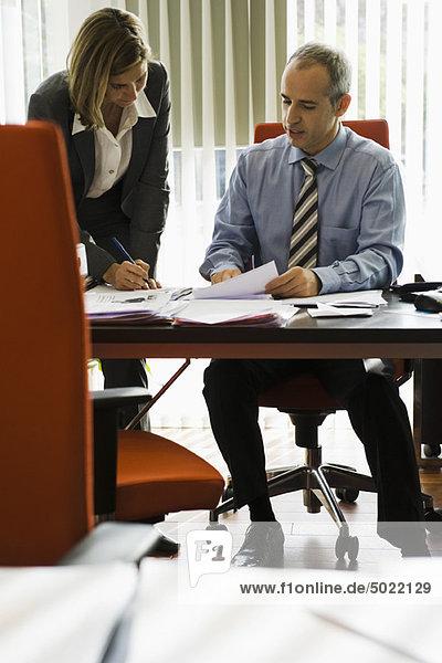 Geschäftsmann im Gespräch mit einer Kollegin  die sich Notizen macht