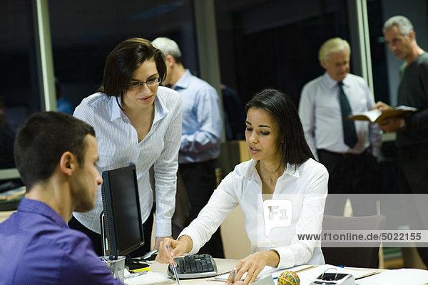 Kollegen arbeiten nachts im Büro zusammen