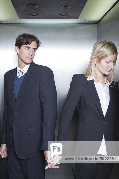 Ein Paar in Geschäftskleidung  das im Aufzug Händchen hält.