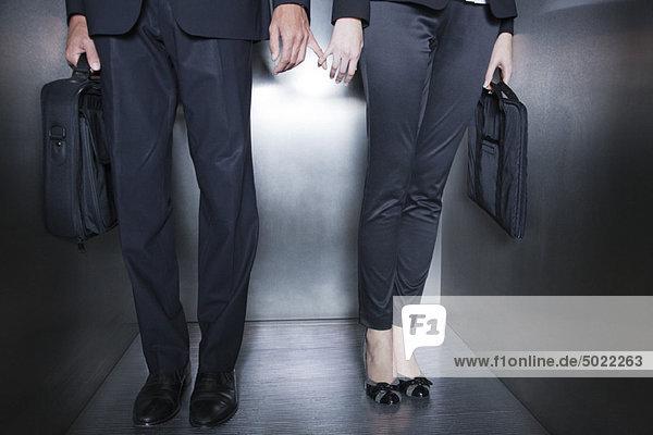 Kollegen halten sich an den Händen im Aufzug  Unterteil
