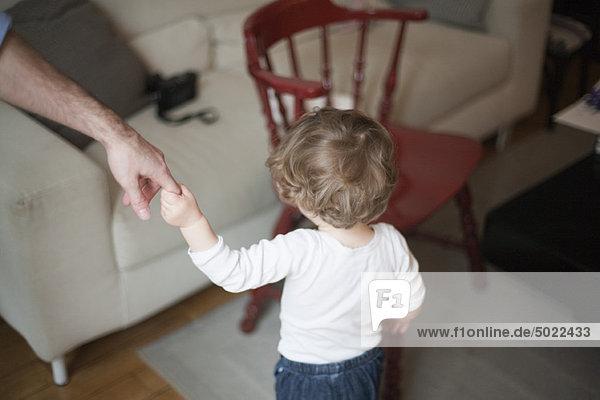 Kleinkind hält sich an Vaters Hand fest  geht auf das Sofa zu  abgeschnitten