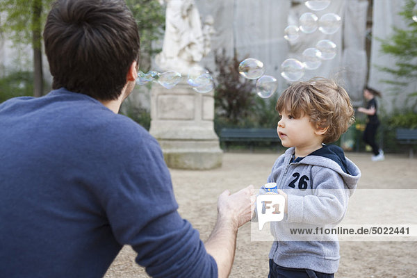 Father and toddler son playing with bubbles