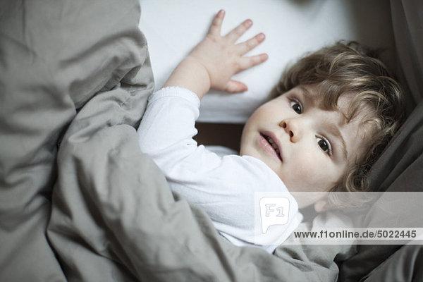 Kleinkind Junge im Bett liegend  Portrait
