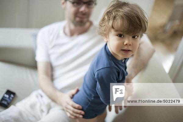 Kleinkind Junge auf Couch mit Vater  Blick in die Kamera