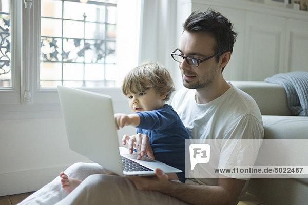 Vater und Sohn schauen zusammen auf den Laptop.