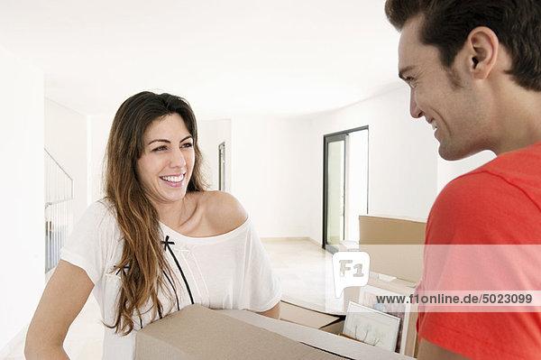 Paar trägt schwere Kiste ins neue Zuhause