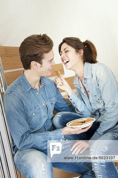 Paar bei einem Snack auf der Treppe