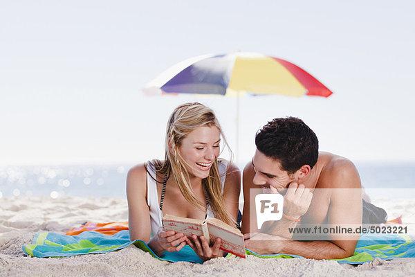 Paar Lesebuch zusammen am Strand