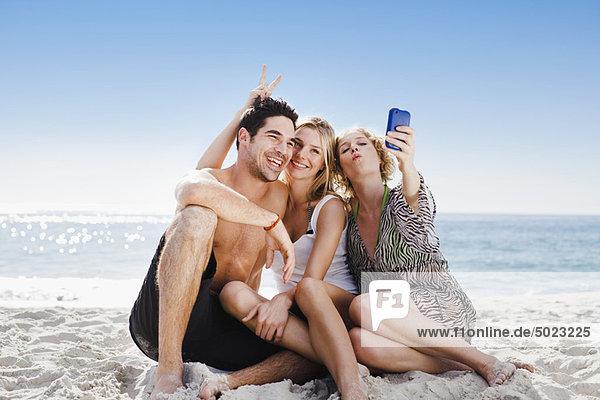 Leute  die am Strand fotografieren