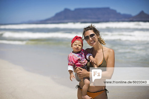 Woman carrying baby girl on beach