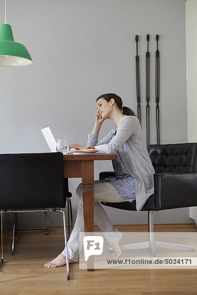 Woman using laptop in dining room