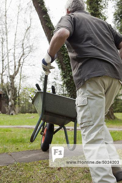Mann schiebt Schubkarre im Hinterhof