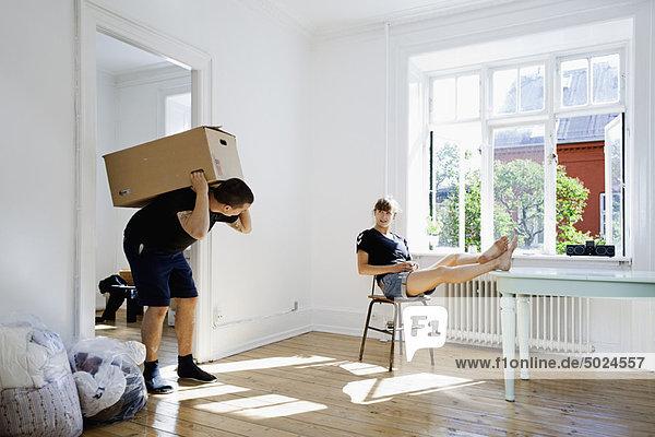 Frau beobachtet Freund tragen schwere Kiste