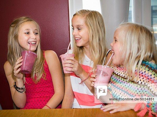 Three sisters drinking milk shakes
