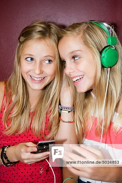 Twin girls listening to music from mp3 player