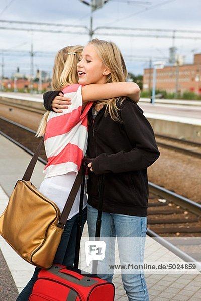 Twin girls saying goodbye to on railway platform