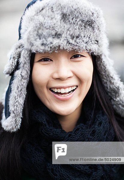 Portrait of happy young woman wearing fur hat