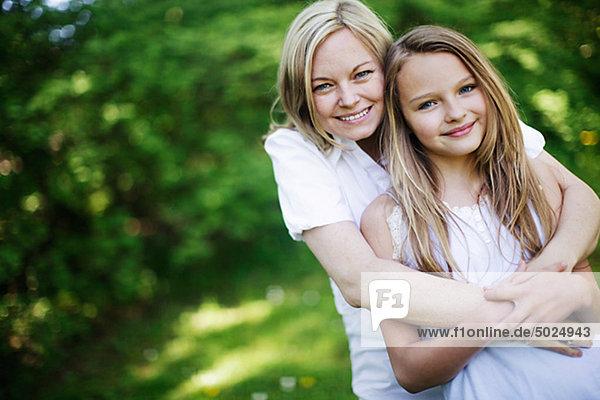 Mutter umarmt Tochter  Lächeln  portrait