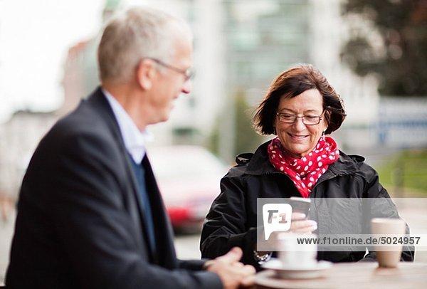 reifes Paar im Cafe  Frau Text messaging auf dem Telefon sitzen