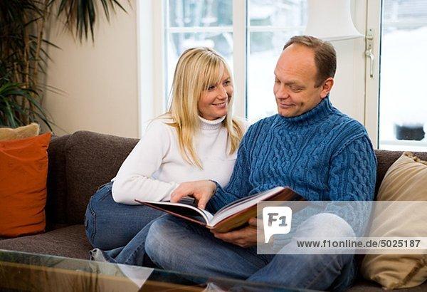 Paar auf Sofa sitzen und lesen