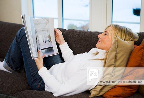 Frau auf der Couch liegen und lesen