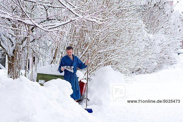 Mann im Bademantel überprüfen Mail im verschneiten Hof