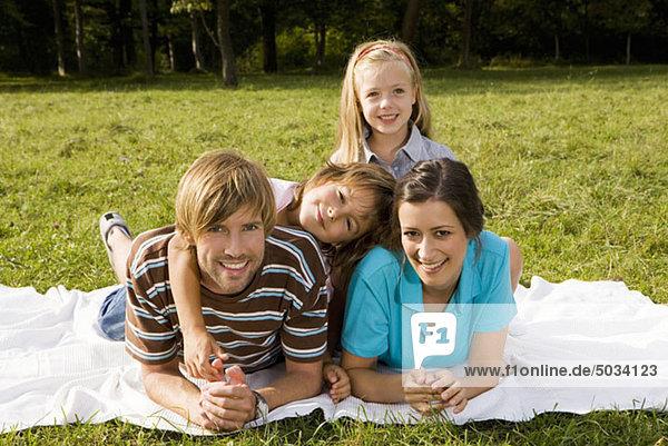 Glückliche Familie liegt auf einer Decke im Gras  München  Bayern  Deutschland