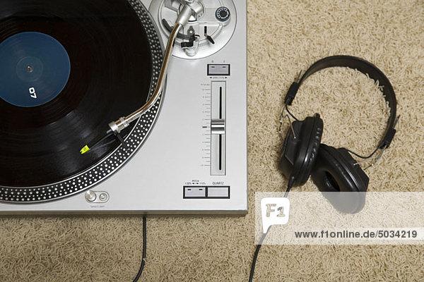 Plattenspieler und Kopfhörer auf einem Teppich