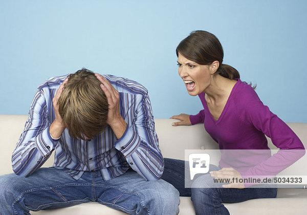 Mann hält sich die Ohren zu  Frau schreit ihn an