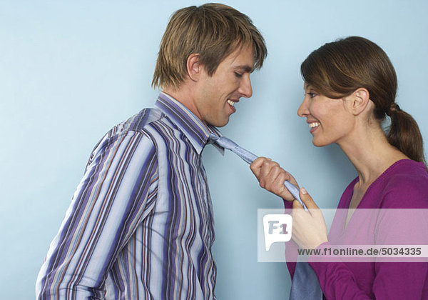 Woman pulling man's tie