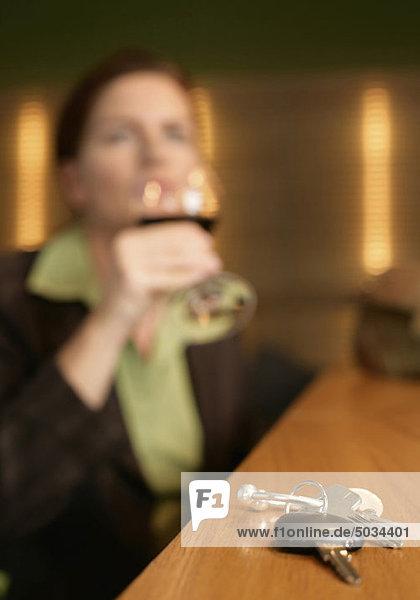 Frau trinkt Rotwein  Autoschlüssel liegen im Vordergrund