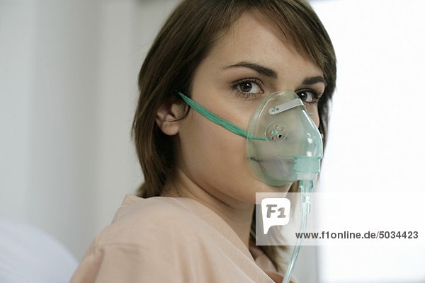 Junge brünette Frau mit einer Beatmungsmaske im Krankenbett - Intensivstation