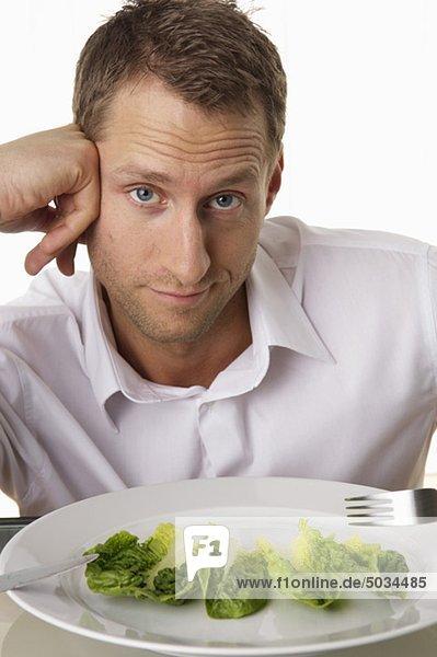Mann isst Salatblätter mit Messer und Gabel - Diät