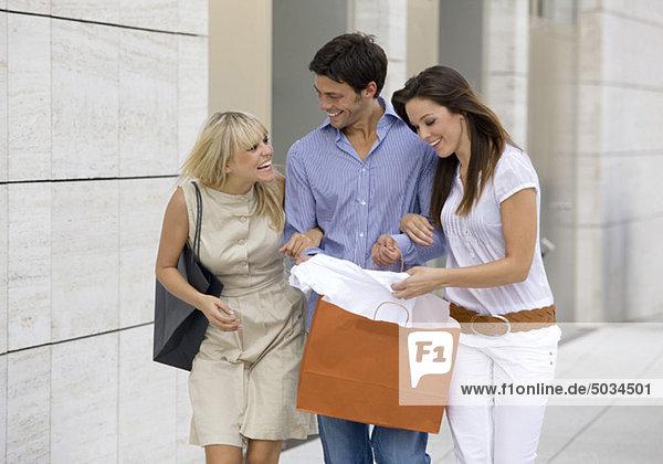 Zwei fröhliche Frauen und Mann in der Stadt mit Einkaufstasche