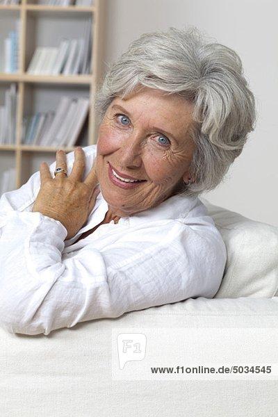 Lächelnde Seniorin auf der Couch