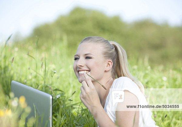 Glückliche e junge Frau liegt mit Laptop auf Wiese
