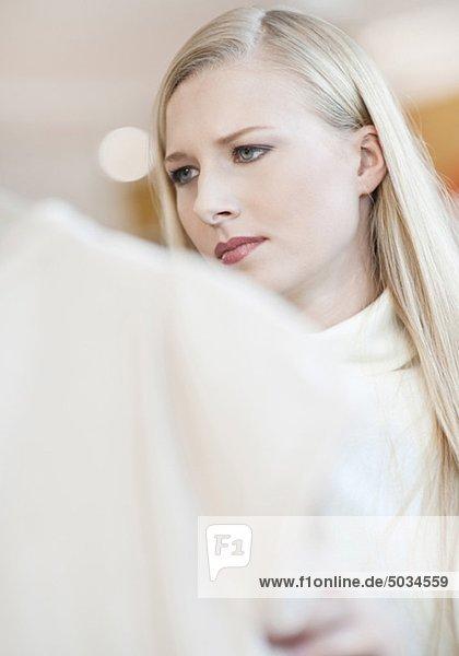 Ernste junge Frau in einem Kleidergeschäft